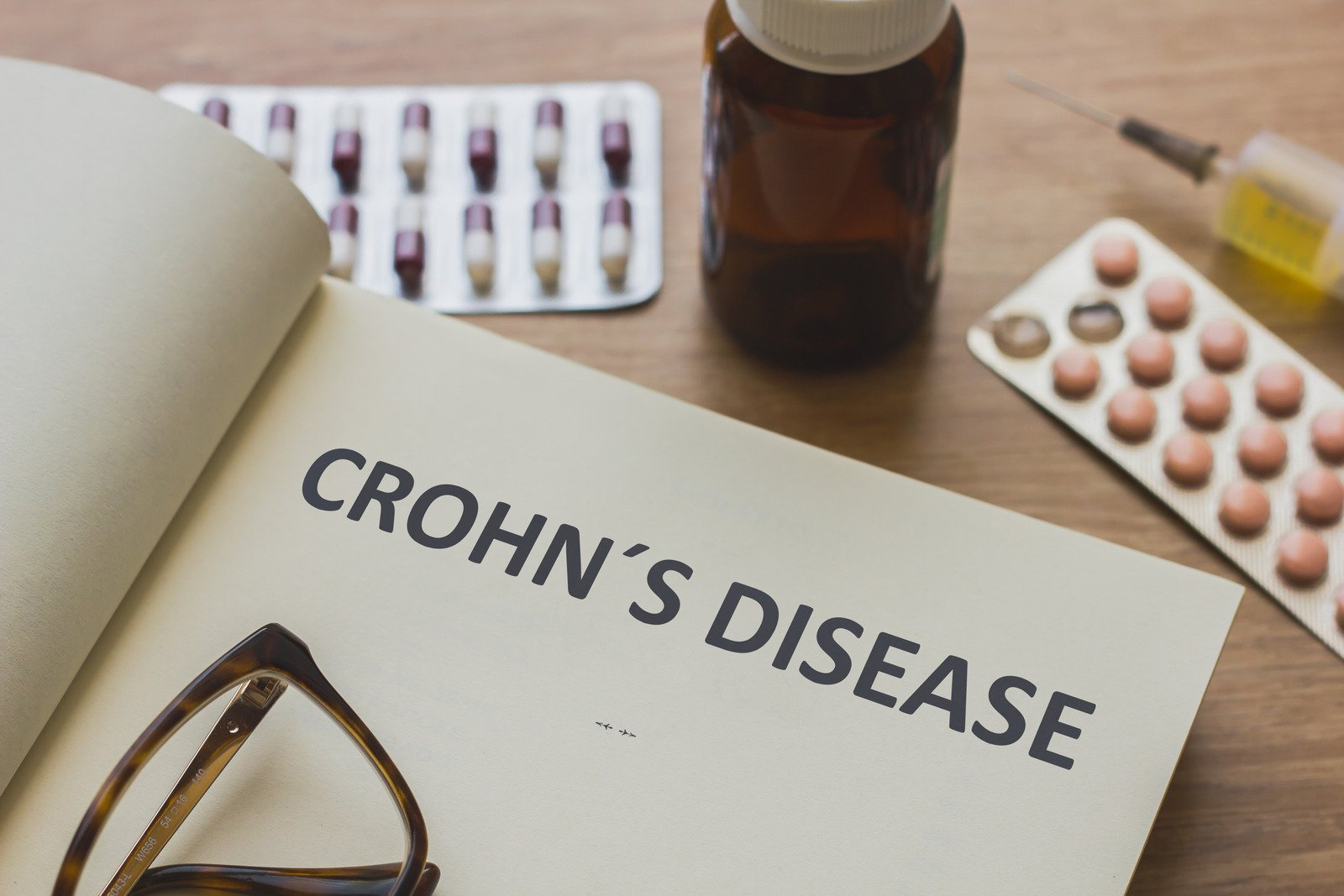 Book about Crohn´s Disease and medication, injection, syringe and pills. Medic concept